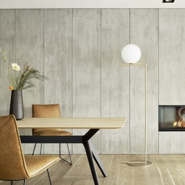 Esstisch mit schwarzem Holzgestell und Platte in Eiche hell, Stehleuchte in Messing und Paneelwand betongrau mit Kaminofen integriert