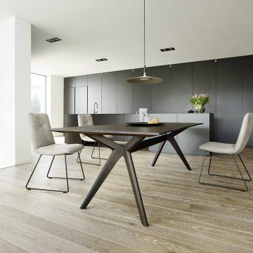 Tisch in Eiche schwarz mit drei Polstersessel, dahinter schwarze Paneelwand raumhoch