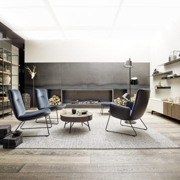 Lounge-Sessel Gruppe mit blauen Bezugsstoff, dahinter Kaminofen in einer Stahlblechwand interiert, links Regal Metall mit Holzfächer