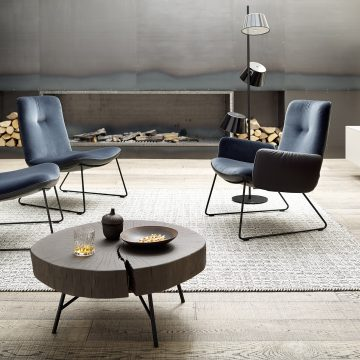 Lounge-Sessel Gruppe mit blauen Bezugsstoff, dahinter Kaminofen in einer Stahlblechwand interiert