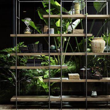 Metallregal mit dicken Holzfächern in Massivholz und raumhohen Zimmerpflanzen dahinter