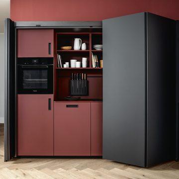Einbauschrank mit Einschubtüren und integrierten Geräten, schwarz matt und rot kombiniert