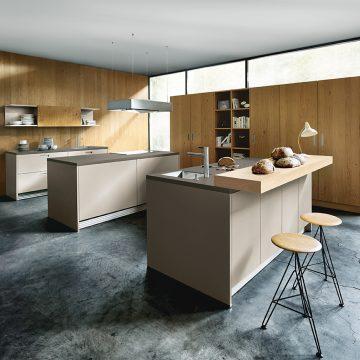 Küche mit Arbeitsinsel und Hochschrank mit Einschubtüren und integrierten Einbaugeräten
