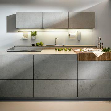 Einbauküche mit Kochinsel in griffloser Ausführung in Keramik Beton grau Nachbildung, mit Arbeitsfläche in Massivholz