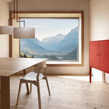 Esstisch Bondt mit Stuhl Nonoto und mit einer roten Anrichte, dahinter Panoramafenster mit Blick ins Gebirge